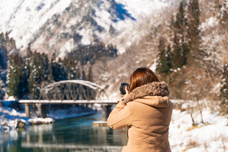 Woman photographing bridge over river against snowcapped mountains