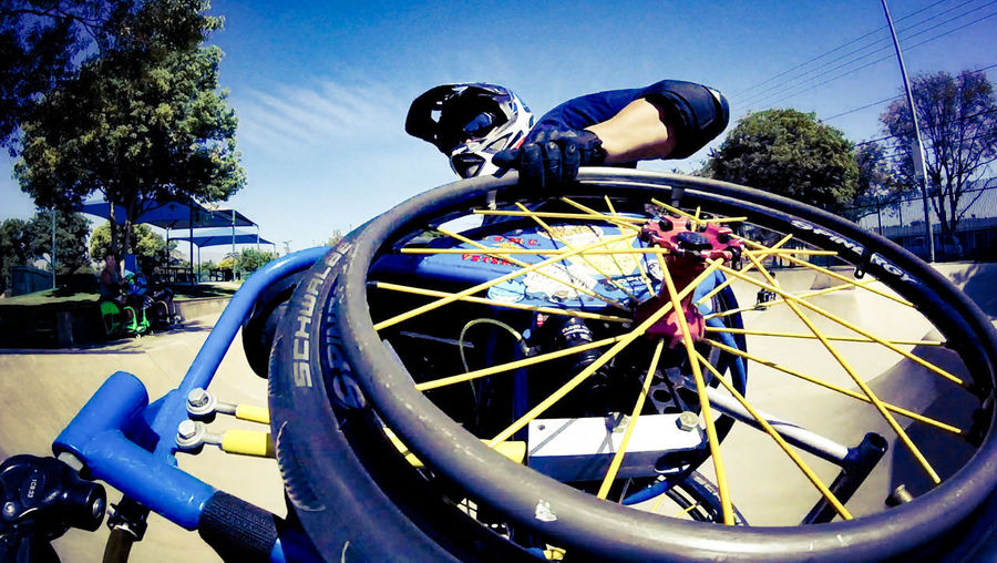 Low angle view of bicycle wheel against blue sky