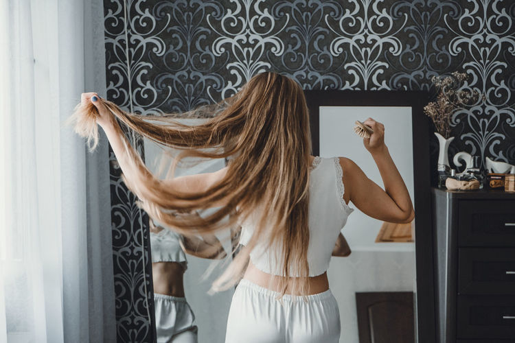 Rear view of woman combing hair at home