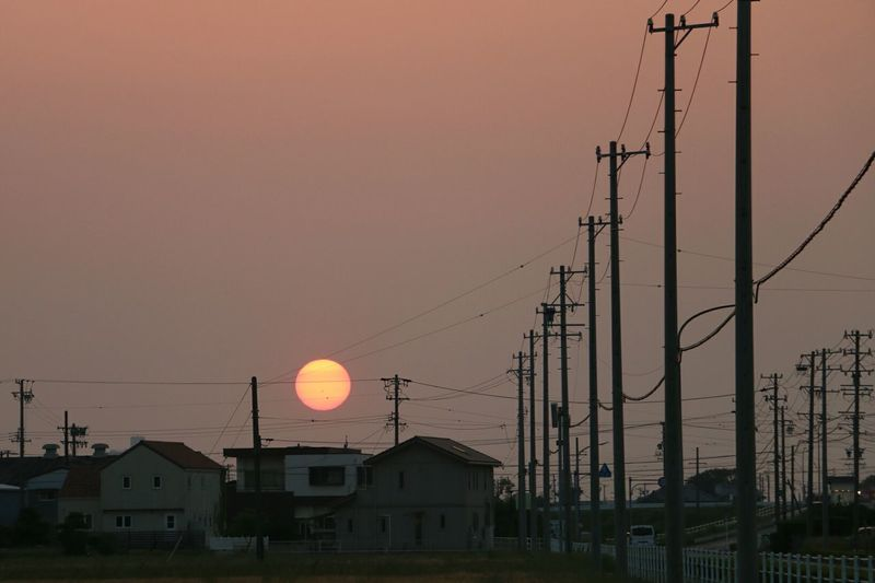 Power Lines By Houses Against Sky During Sunset