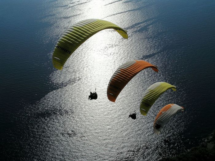 High angle view of paraglidings over sea
