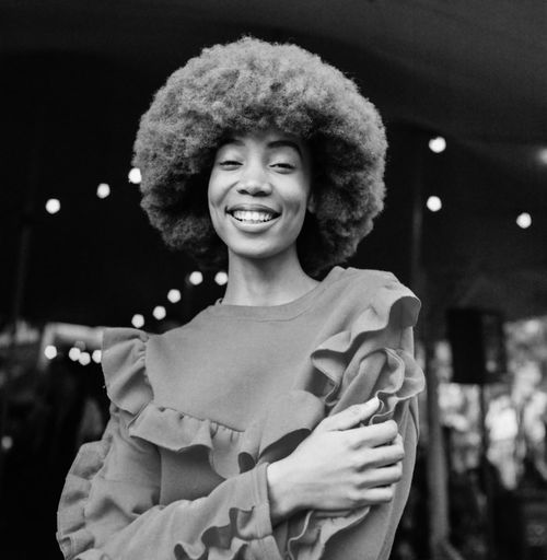 Afro Queen The Portraitist - 2018 EyeEm Awards TheWeekOnEyeEM Beautiful Woman Cheerful Curly Hair Emotion Film Photography Focus On Foreground Front View Hairstyle Happiness Indoors  Lifestyles Looking At Camera Night One Person Portrait Real People Smiling Standing Waist Up Women Young Adult