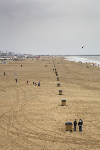 Scenic View Of Beach With People Against Sky