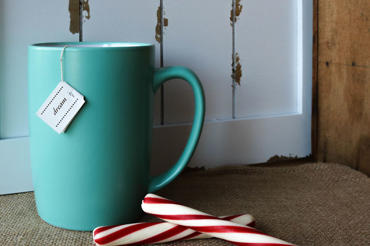 Close-Up Of Drink With Candy Canes On Table
