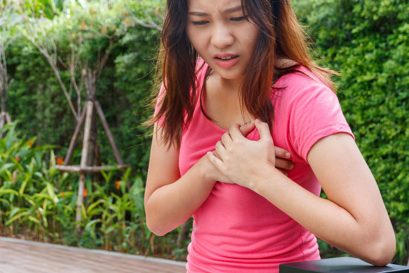 Young woman suffering from chest pain