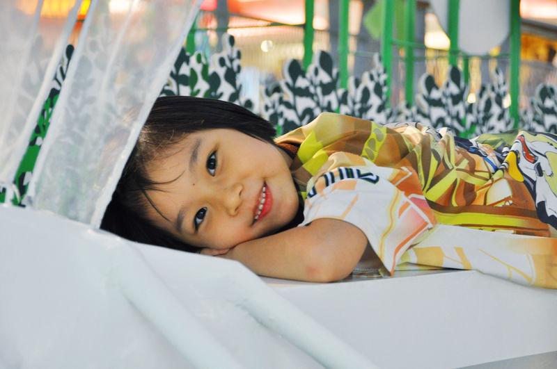 Portrait of cute boy lying on bed