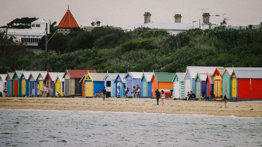 People by beach huts on shore