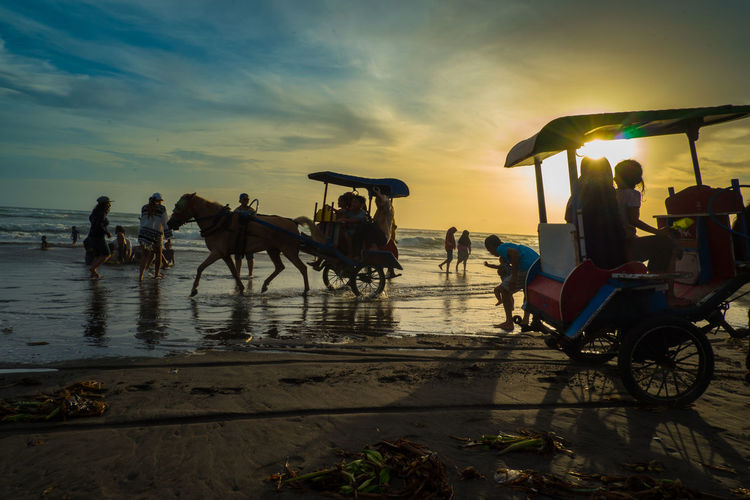 People riding bicycles on beach against sky during sunset