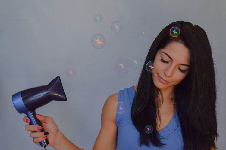 Woman using hair dryer by bubbles in mid-air by white wall