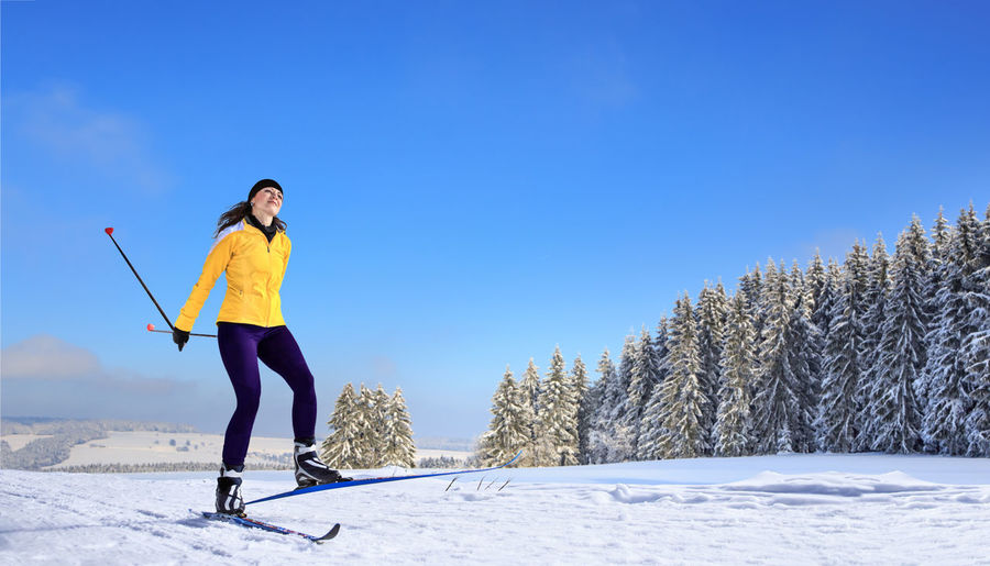 A woman at cross-country skiing or langlauf running in the wintry forest Action, Activity, Adult, Competition, Cross-country, Exercise, Female, Fit, Forest, Girl, Healthy, Langlauf, Lifestyles, Nordic, Person, Running, Skating, Skiing, Snow, Sports, Style, Training, Winter, Wintry, Woman Winter Cold Temperature Snow One Person Real People Lifestyles Leisure Activity Young Adult Nature Field Land Warm Clothing