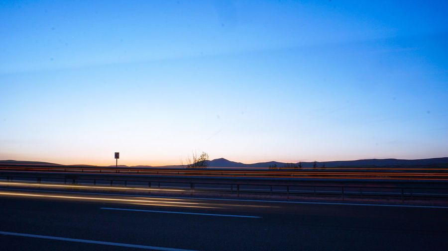 Road Mountain Sunset Blue Clear Sky Motion Long Exposure Traffic Highway Illuminated Elevated Road Viaduct Two Lane Highway Road Intersection High Street Tail Light Light Trail Vehicle Light Multiple Lane Highway Overpass Winding Road Mountain Road Cable-stayed Bridge Office Building