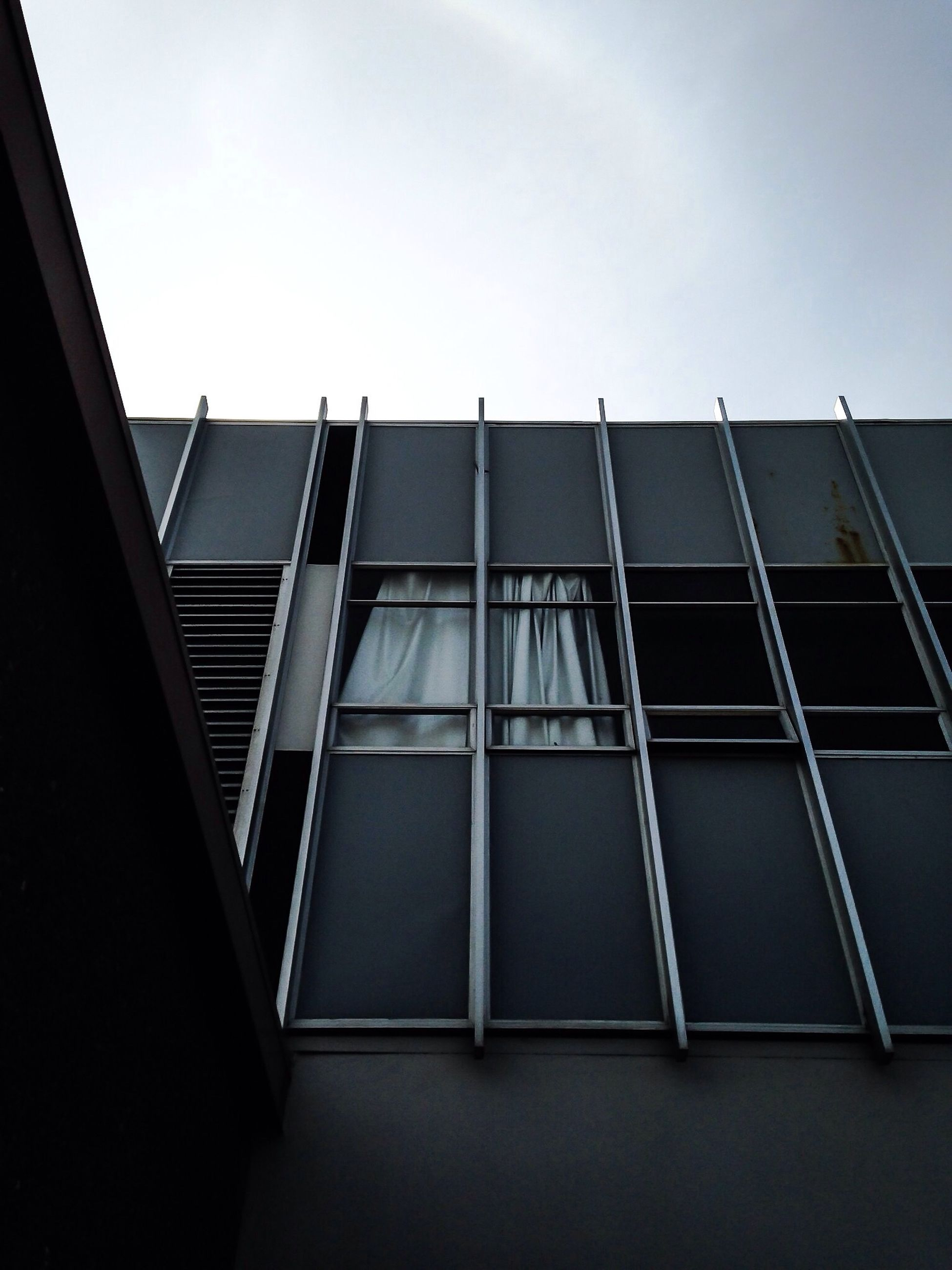 architecture, building exterior, built structure, low angle view, window, building, glass - material, modern, sky, clear sky, office building, city, residential building, residential structure, day, no people, reflection, outdoors, glass, architectural feature
