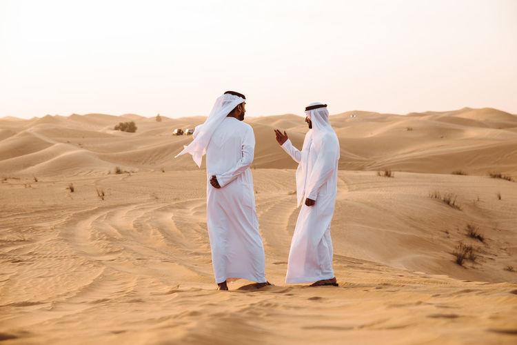 Rear view of men on sand dune in desert against sky