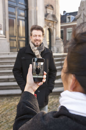 Portrait of man photographing while using smart phone in city