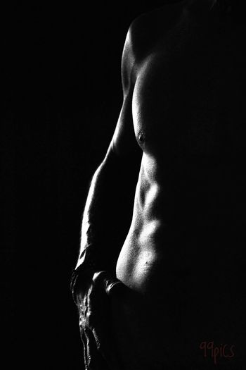 Midsection of muscular man against black background