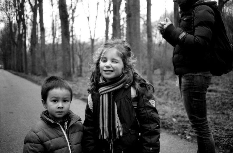 Portrait of girl winking while standing by brother on road during winter
