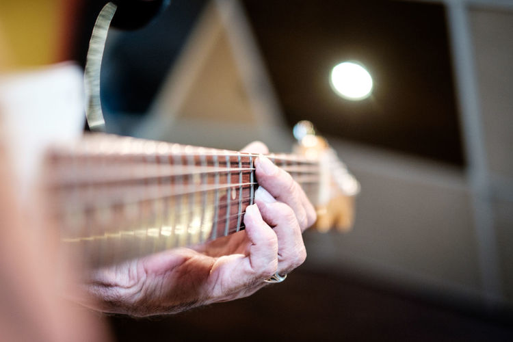 Close-up of senior person playing guitar