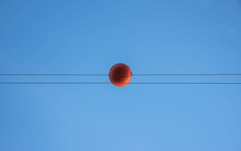 Low angle view of cables with orange equipment against clear blue sky