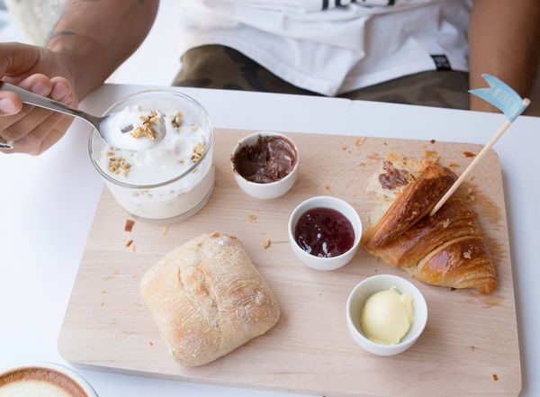 High Angle View Food And Drink Table Indoors  One Person Plate Indulgence Sweet Food People Food Eating Day Human Body Part Freshness Human Hand Ready-to-eat Brunch Yogurt Healthy Eating Breakfast White Color White Background Bread Croissant Half Eaten