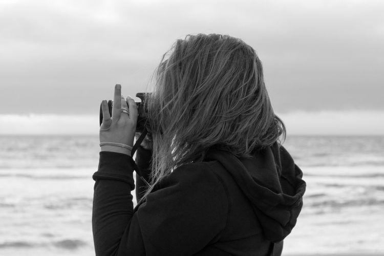Side view of woman photographing while standing at beach against sky