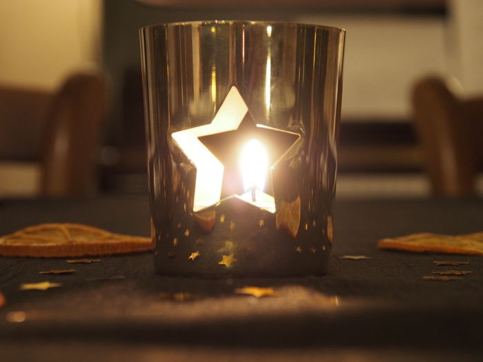 Close-up of illuminated candle on table at home