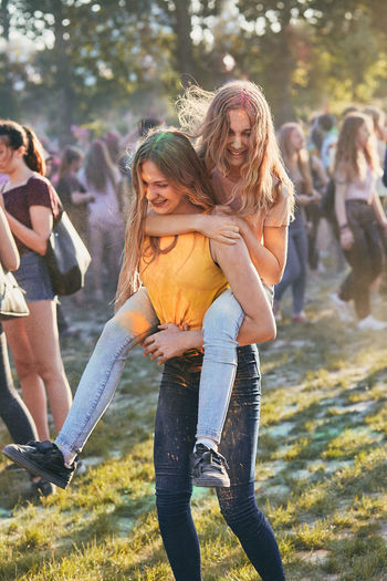 Teenage girl giving friend piggyback ride while standing outdoors