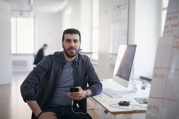 Portrait of male engineer holding mobile phone while sitting at computer desk in office