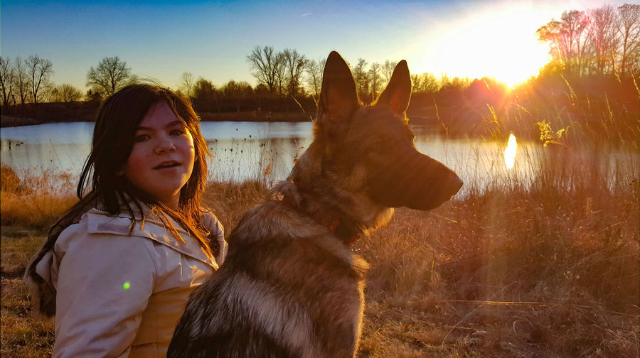 Portrait of girl with dog on grass against sky during sunset