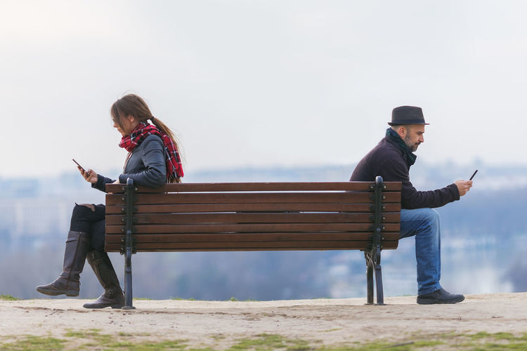 People using smart phones while sitting on bench at observation point
