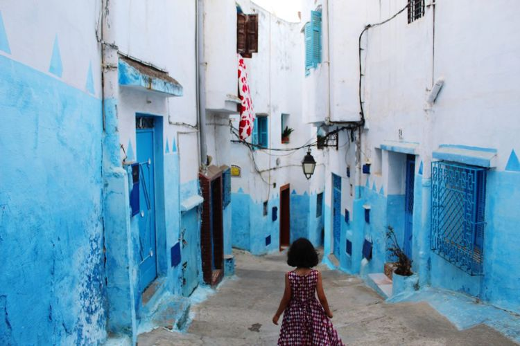 Rear view of girl walking on steps amidst buildings