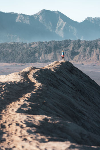 Man standing on mountain at arid landscape