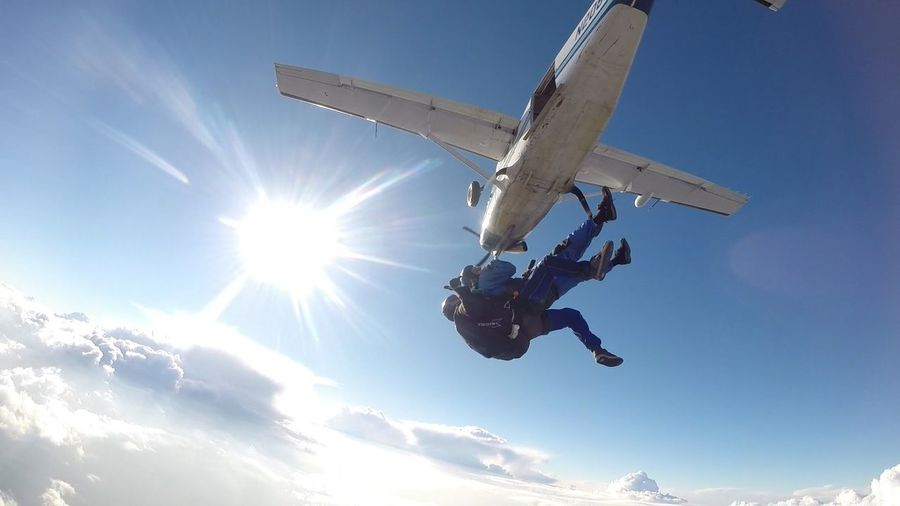 Low angle view of skydiver jumping from airplane against sky on sunny day