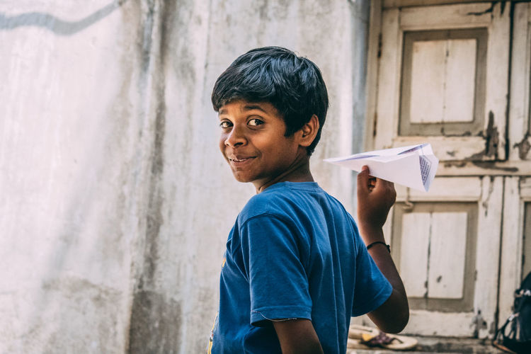 Portrait of boy holding paper airplane against wall