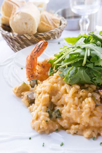 Close-up of fresh prawns risotto served with arugula in plate on table