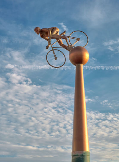 HIGH RIDER: Bronze-effect statue of Bill Bradley (1933-1997), a famous local racing cyclist. Southport, Merseyside. By Eaton Waygood Associates. Memorial Sunlit High Clouds Pedestal Man Cyclist Speed Pedalling Racing Bicycle Cloud - Sky Day Low Angle View Metal No People Outdoors Pillar Sky