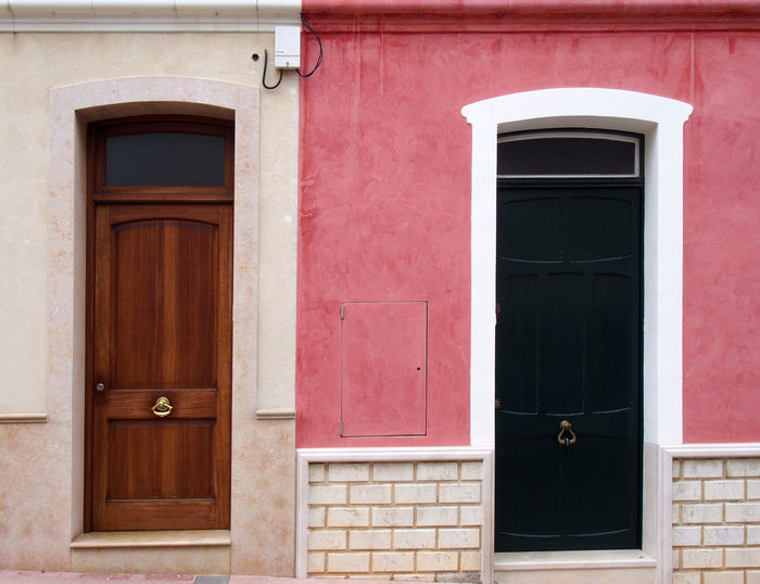 two neighboring different colored front doors next to each other in residential old houses painted in pink and white Built Structure Door Entrance Building Exterior Architecture Building Window No People House Day Security Safety Protection Residential District Closed Wood - Material Outdoors Front Door Red Wall - Building Feature Two Objects Neighbors