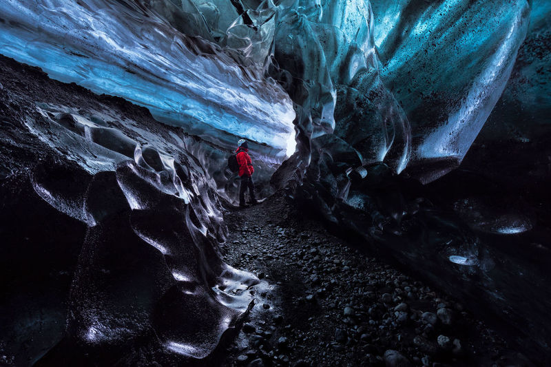 Person standing on rock in cave