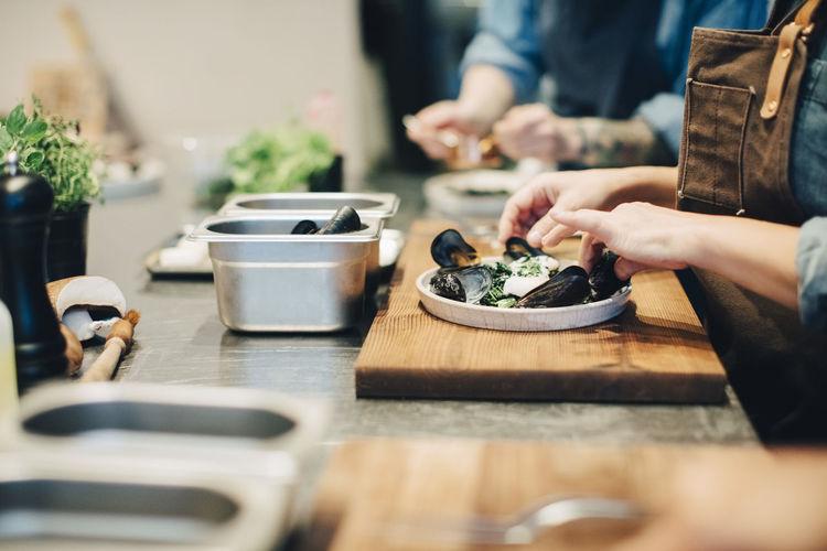 People preparing food on table in kitchen