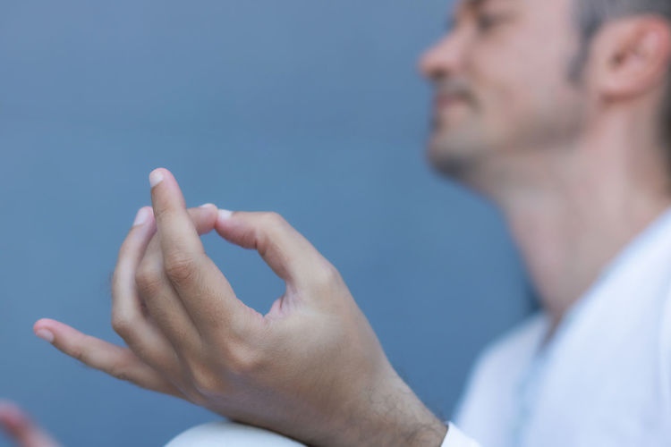 Close-up of man hand against blue sky