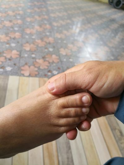 Cropped hand of person holding child foot