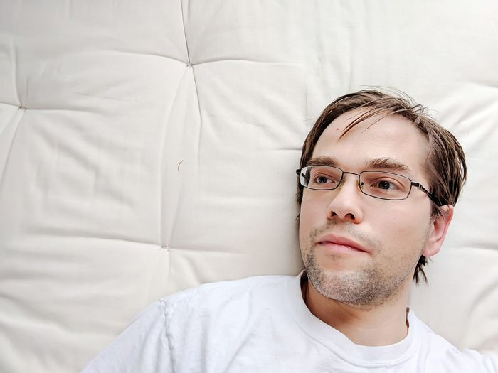 Portrait of young man with tattoo on bed