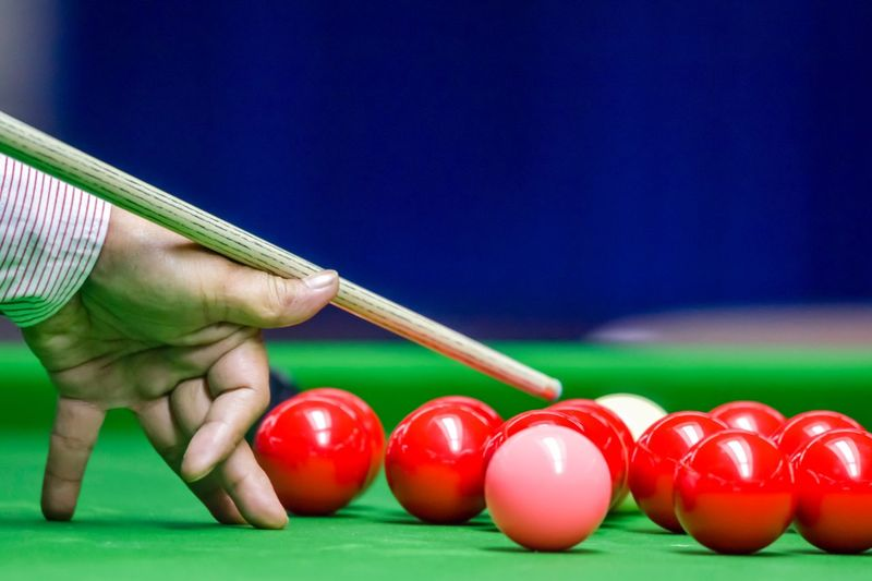 Cropped hand playing ball on pool table