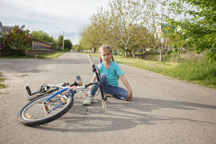 Boy riding bicycle on road in city