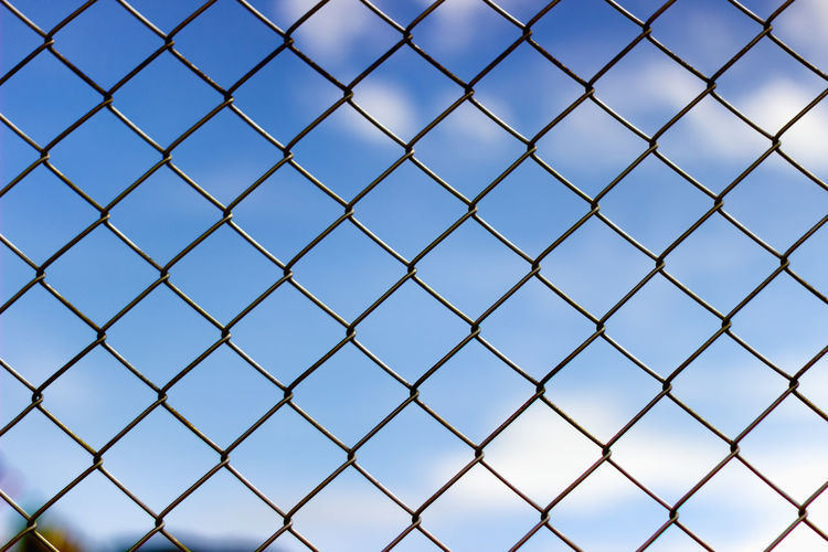 Full Frame Shot Of Chainlink Fence Against Blue Sky