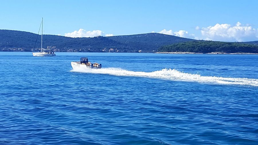 Sunny Nautical Vessel Blue Sea Water Mountain Horizontal Outdoors Clear Sky Day Person Adventure Sky People Sailboat Yachting Adult Nature Catamaran Cityscape