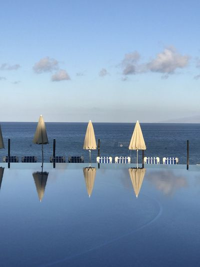 Deck chairs by swimming pool against sky