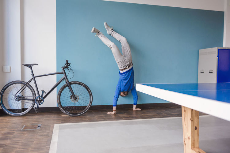 Man leaning on bicycle against wall