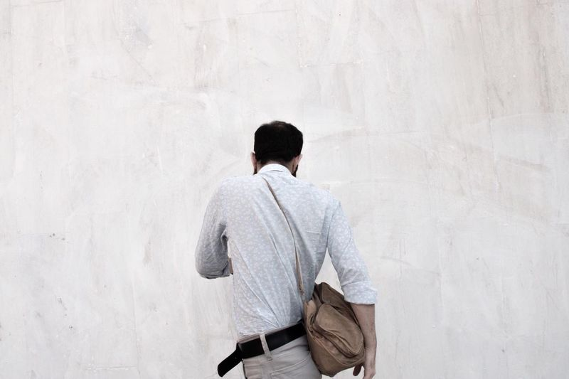 Rear view of man standing against white wall
