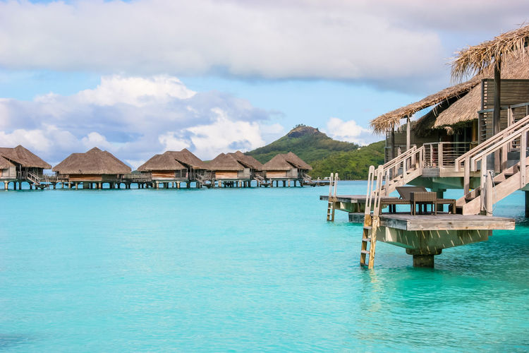 View of Mt. Pahia with overwater bungalows in Bora Bora Architecture Blue Bora Bora  Built Structure Clouds French Polynesia Lagoon Mountain Overwater Bungalow Thatched Roof The Essence Of Summer Volcano Water Summer Landscapes Feel The Journey