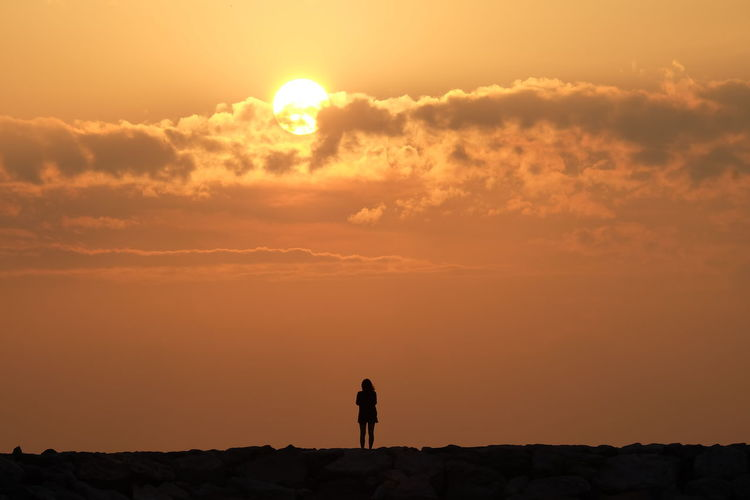 Silhouette Of Woman Standing On Landscape At Sunset